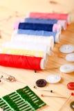 Diversos hilos y otros accesorios de costura en tablero ligero Imagen de archivo libre de regalías