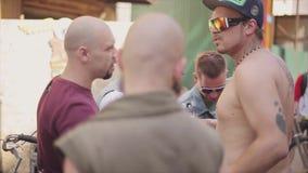 Diversos homens adultos ficam nos punhos da batida da rua beard sunglasses Encontro dos motociclistas Dia ensolarado do verão filme