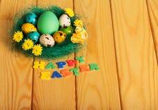 Diversos huevos coloridos en la jerarquía y la inscripción PASCUA FELIZ imagen de archivo