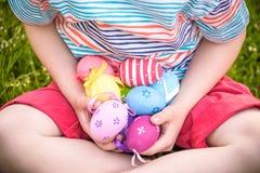 Diversos huevos de Pascua del color en manos del ` un s del niño egg caza Imagen de archivo