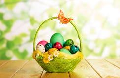 Diversos huevos de Pascua en cesta y mariposa en verde abstracto Imagen de archivo