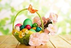 Diversos huevos de Pascua en cesta y rama con las flores Fotografía de archivo