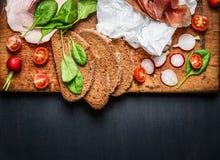 Diversos ingredientes para el bocadillo de la carne y de jamón en fondo de madera oscuro Imagen de archivo
