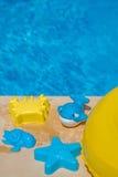 Diversos juguetes del agua en el lado de una piscina Foto de archivo libre de regalías