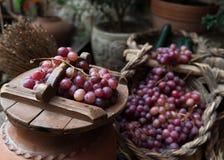Diversos manojos de uvas rojas en cesta de mimbre Imagen de archivo