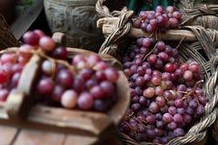 Diversos manojos de uvas rojas en cesta de mimbre Foto de archivo libre de regalías