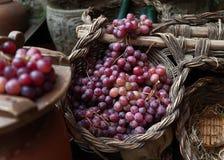 Diversos manojos de uvas rojas en cesta de mimbre Fotos de archivo