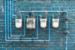 Diversos medidores de gás situados na parede de uma construção residencial foto de stock