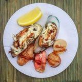 Diversos mexilhões fritados, de duas partes da carne de caranguejo e de diversas vieiras do alto mar com limão encontram-se em um Imagens de Stock