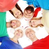 Diversos muchachos y muchachas en sombreros de la Navidad que abrazan juntas aislados en blanco Imagen de archivo libre de regalías
