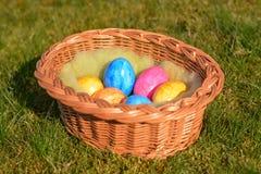 Diversos ovos da páscoa coloridos em uma cesta na grama Fotografia de Stock Royalty Free