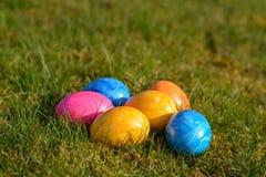 Diversos ovos da páscoa coloridos que encontram-se na grama Imagens de Stock