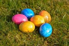 Diversos ovos da páscoa coloridos que encontram-se na grama Imagem de Stock Royalty Free