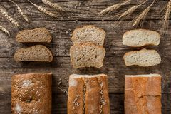 Diversos pan fresco y espiguillas del trigo en fondo de madera rústico Disposición creativa hecha del pan imagenes de archivo