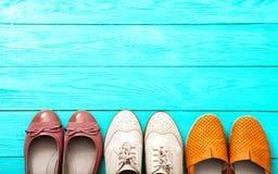 Diversos pares de zapatos femeninos en piso de madera azul, la visión superior y el espacio de la copia Mofa para arriba Fotografía de archivo