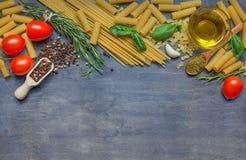 Diversos pastas, condimento, queso, aceite de oliva y tomates en DA Foto de archivo