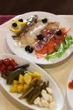 Diversos pescados de mar salados con las aceitunas y el limón, verduras conservadas en vinagre en las placas en la tabla de banqu Foto de archivo libre de regalías