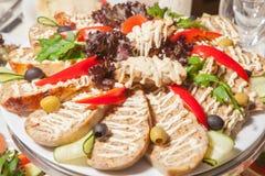 Diversos platos de la comida en las tablas Imagen de archivo libre de regalías