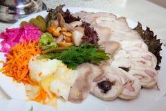 Diversos platos de la comida en las tablas Foto de archivo
