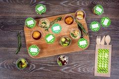 Diversos platos en envase de plástico y cubiertos de madera en la tabla Foto de archivo