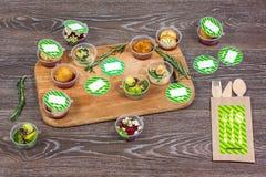 Diversos platos en envase de plástico y cubiertos de madera en la tabla Fotografía de archivo