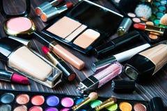 Diversos productos de maquillaje en fondo oscuro fotos de archivo