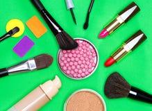 Diversos productos de maquillaje en fondo verde Imagen de archivo libre de regalías