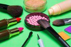 Diversos productos de maquillaje en fondo verde Imágenes de archivo libres de regalías