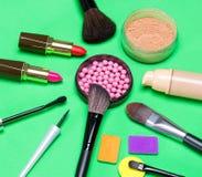 Diversos productos de maquillaje en fondo verde Foto de archivo libre de regalías