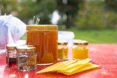 Diversos productos tales como propóleos, placas de la cera de la miel contra fondo borroso fotos de archivo