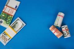 diversos punhados do dinheiro de moedas diferentes em um fundo azul foto de stock royalty free