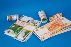 diversos punhados do dinheiro de moedas diferentes em um fundo azul imagem de stock royalty free