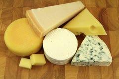 Diversos quesos en un tablero de la cocina Imagen de archivo libre de regalías