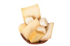 Diversos quesos y un manojo de perejil que miente en un baske de mimbre Foto de archivo libre de regalías