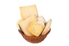 Diversos quesos y un manojo de perejil que miente en un baske de mimbre Foto de archivo