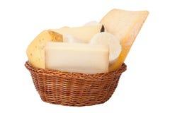 Diversos quesos y un manojo de perejil que miente en un baske de mimbre Imágenes de archivo libres de regalías