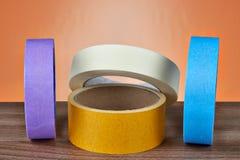 Diversos rolos multi-coloridos da fita adesiva em um backgr alaranjado Fotos de Stock Royalty Free