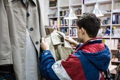 Diversos ropa y bolsos en los estantes y las suspensiones Imagen de archivo libre de regalías
