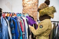 Diversos ropa y bolsos en los estantes y las suspensiones Imagenes de archivo