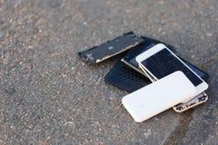 Diversos smartphones quebrados estão no asfalto Imagem de Stock Royalty Free
