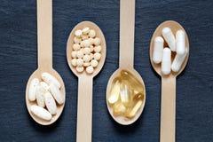 Diversos suplementos sanos en las cucharas de madera Fotos de archivo libres de regalías