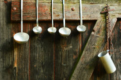 Diversos tamaños de la cucharón que cuelgan en una puerta de madera vieja Imagen de archivo libre de regalías