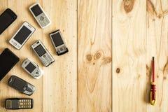 Diversos telefones celulares velhos e novos com chave de fenda imagens de stock