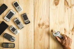 Diversos telefones celulares velhos e novos com mão humana perita foto de stock