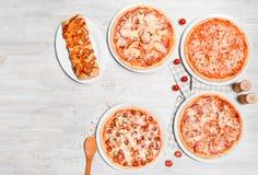 Diversos tipos da pizza são disparados em um fundo de madeira claro Fotografia de Stock