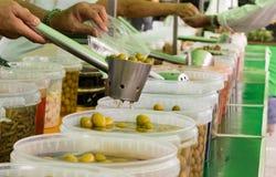 Diversos tipos de aceitunas verdes en un mercado callejero fotos de archivo