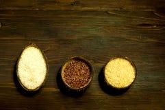 Diversos tipos de arroz en coco natural ruedan en fondo de madera El concepto de comida sabrosa y sana, espacio de la copia imagen de archivo
