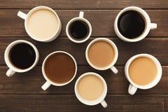 Diversos tipos de café en tazas en la tabla de madera, visión superior Fotos de archivo