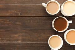 Diversos tipos de café en tazas en la tabla de madera, visión superior Imagen de archivo libre de regalías