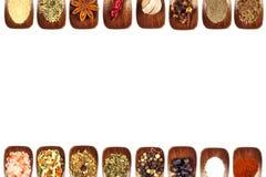 Diversos tipos de especias en una cuchara de madera, aislados en blanco Decoraciones en el menú Venta de especias Espacio de publ Foto de archivo libre de regalías